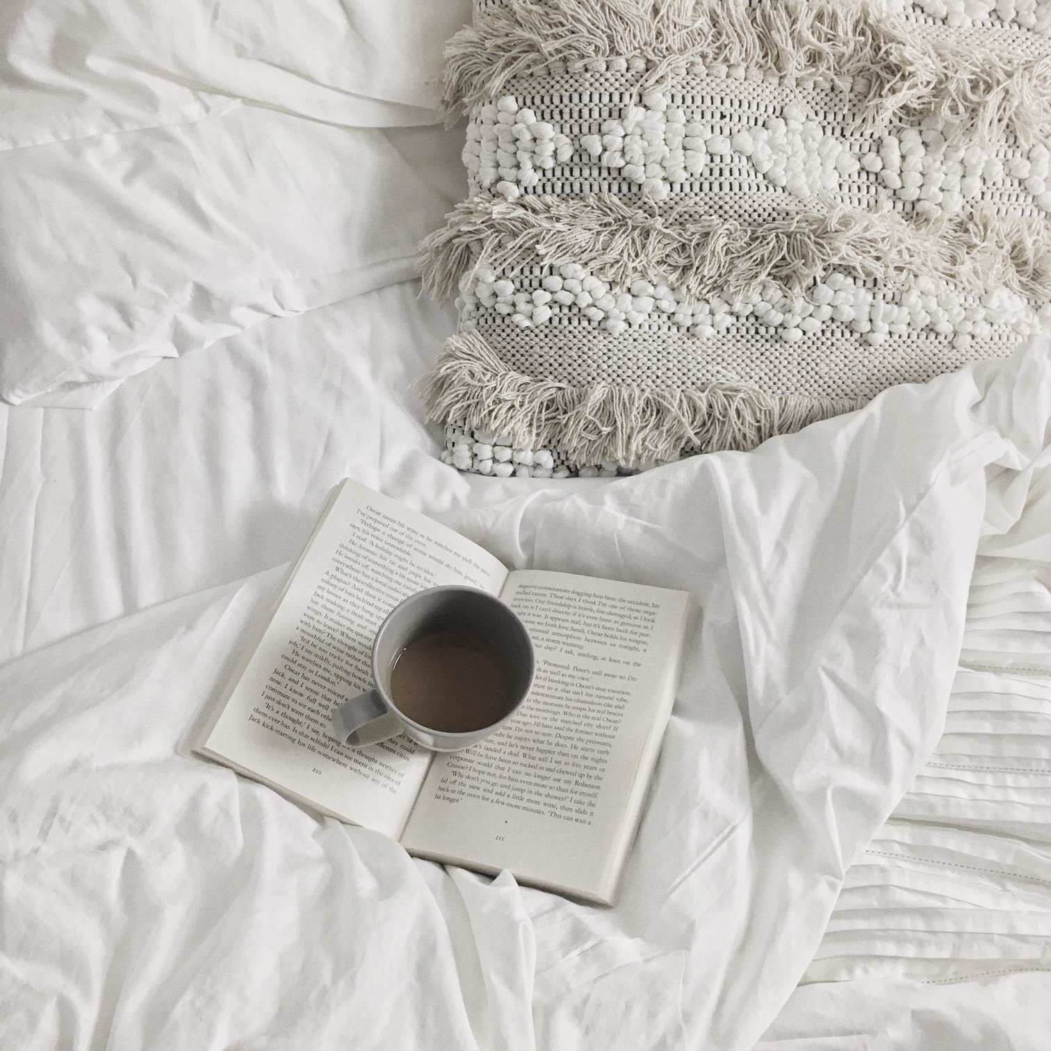 Book and cup of tea of a white duvet