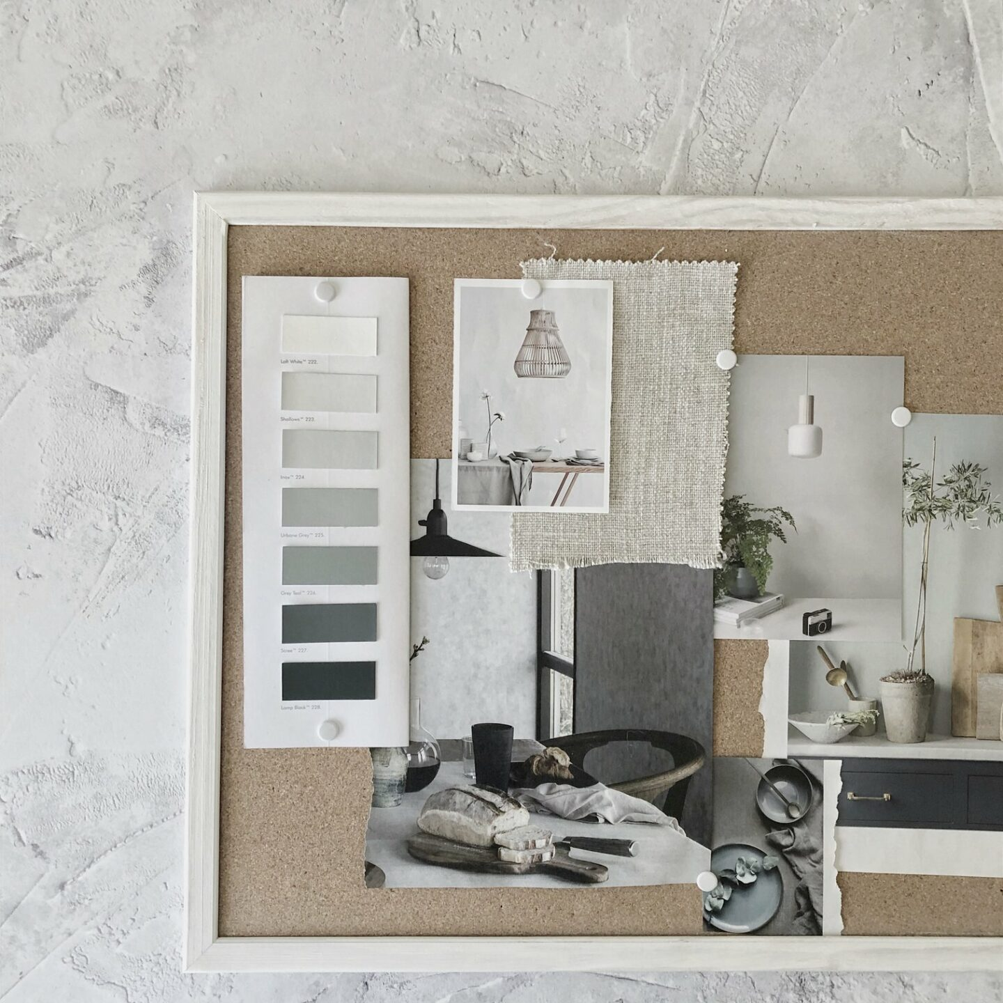 Grey slow living interiors mood board arranged on a cork board