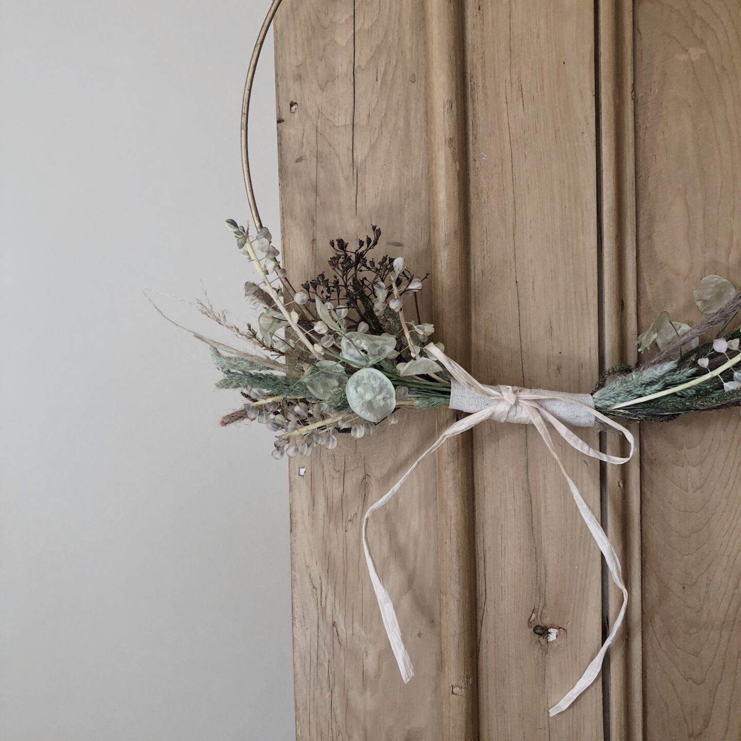Dried flower wreath hanging against cupboard