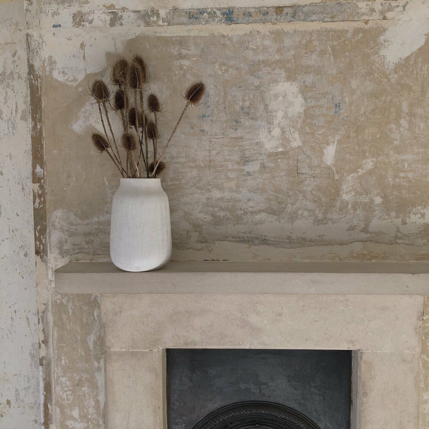 Rustic wallpaper-stripped walls and a vase of teasels